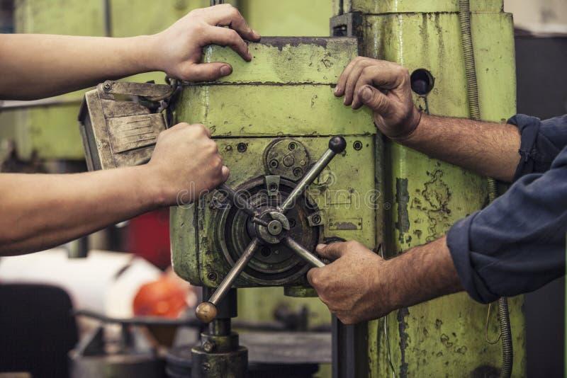 Manliga händer som arbetar vridningen spaken på maskinen i ett gammalt faktum royaltyfri bild