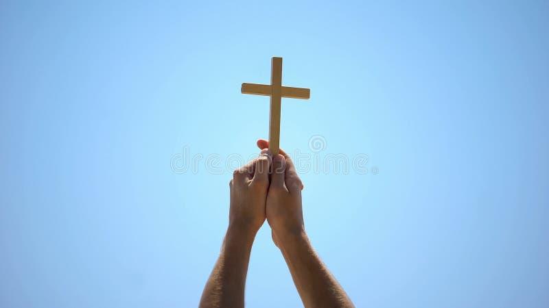Manliga händer som höjer träkors till blå himmel, religiös konvertering, baptism royaltyfria foton