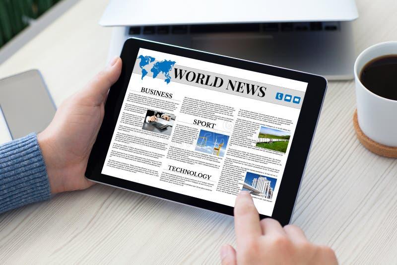 Manliga händer som rymmer minnestavladatorvärldsnyheter, bordlägger anteckningsbokpho royaltyfria bilder