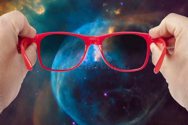 Manliga händer som rymmer solglasögon som ser universumutforskningbegrepp royaltyfri foto