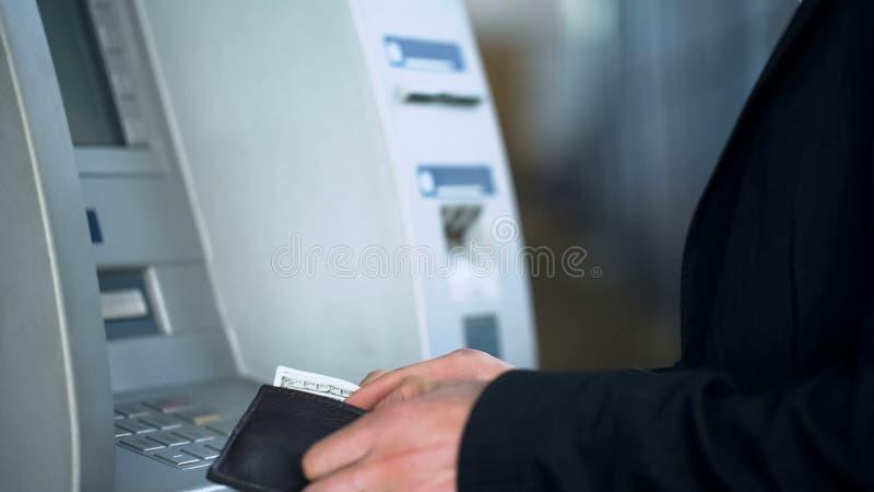 Manliga händer som sätter dollar i handväskan som återtar pengar från bankkonto, ATM arkivbilder
