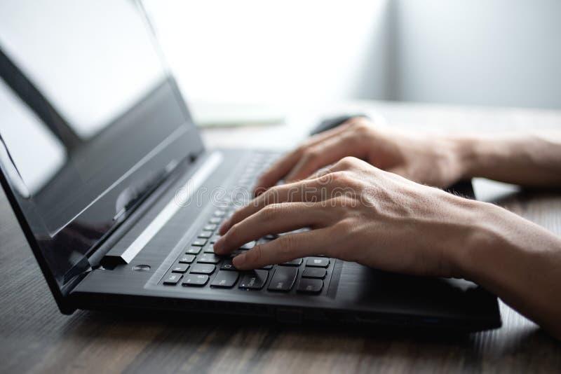 Manliga händer som skriver på det svarta bärbar datordatortangentbordet royaltyfri fotografi