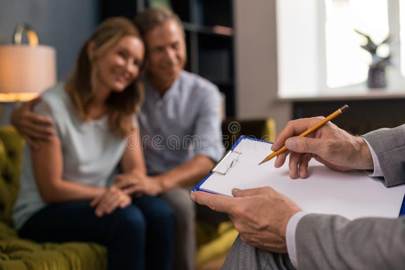 Manliga händer som skriver på papper med en blyertspenna royaltyfri fotografi