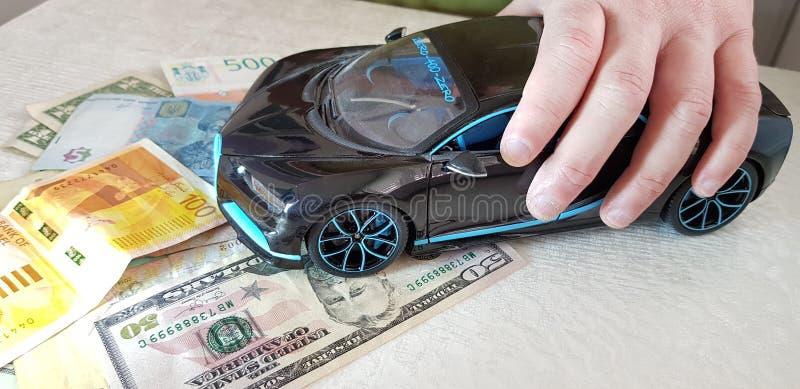Manliga håll i hans för Bugatti Chiron för fingrar svarta anseende för leksak metall med framhjul på pappersdolla royaltyfria bilder