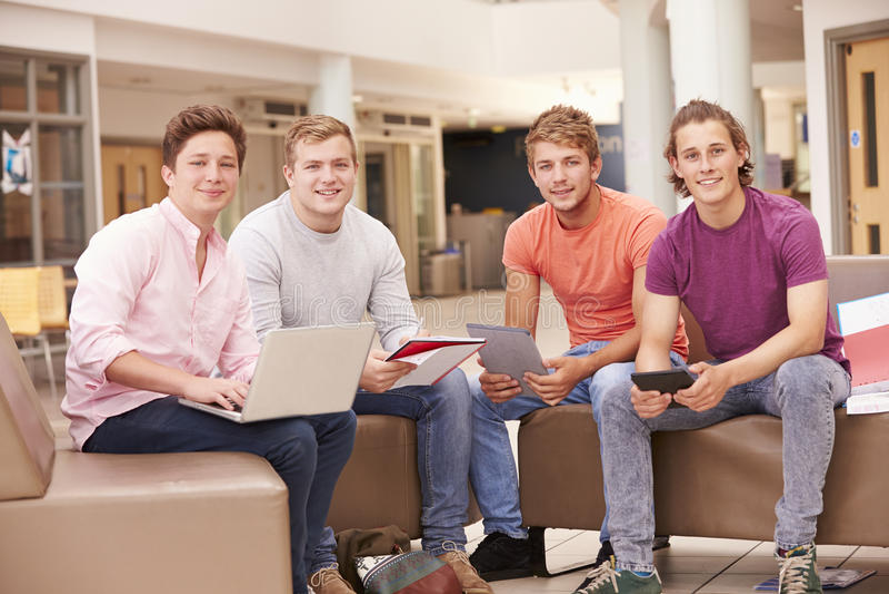 Manliga högskolestudenter som tillsammans sitter och talar royaltyfria foton