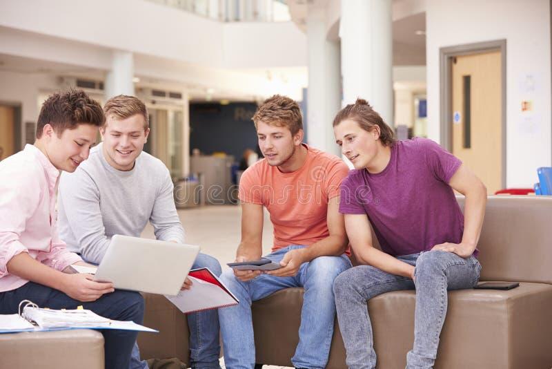 Manliga högskolestudenter som tillsammans sitter och talar arkivbilder