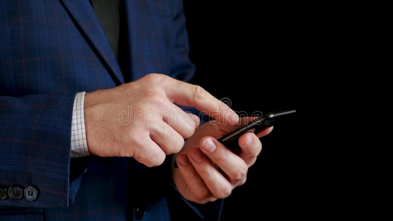 Manliga h?nder som rymmer upp ett svart smartphoneslut royaltyfri bild