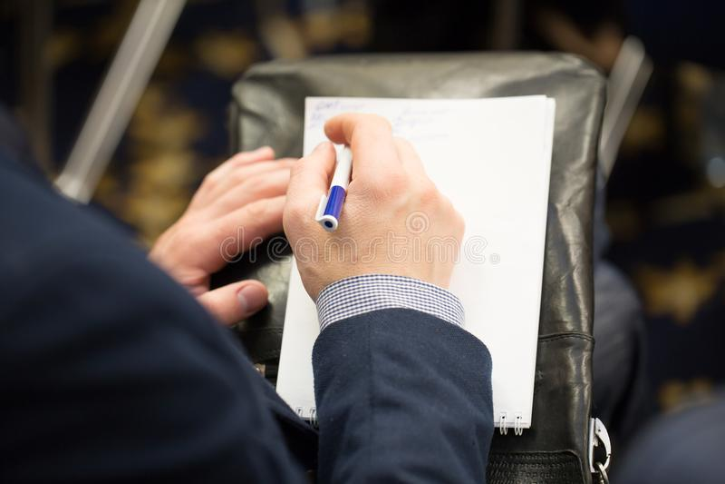 Manliga handhandstilplan i en notepad planerande arbete Framställning av viktiga beslut, projekt ordnings arkivbild