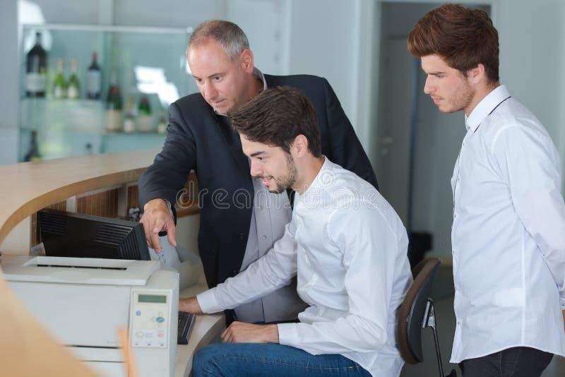 Manliga hotellmottagandearbetare med chefen arkivfoton