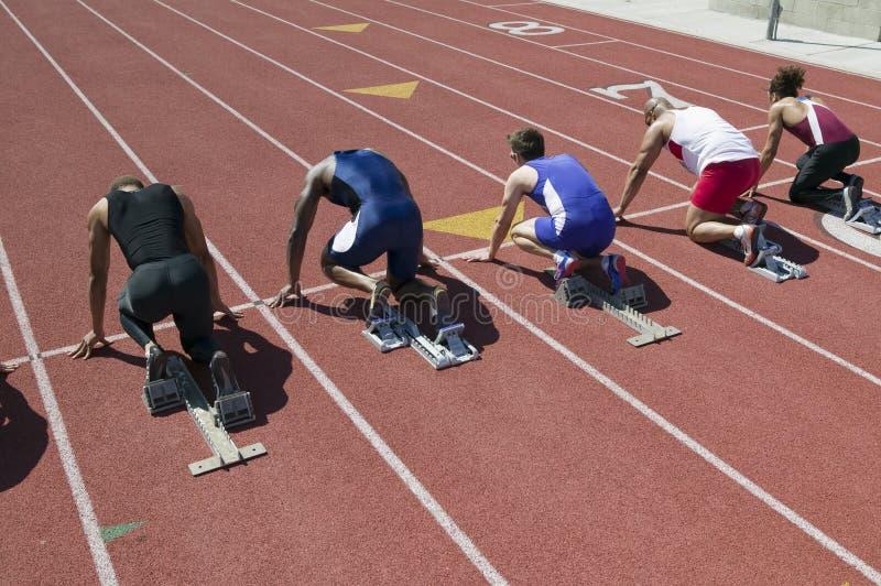 Manliga idrottsman nen på den startande linjen av loppet arkivfoton