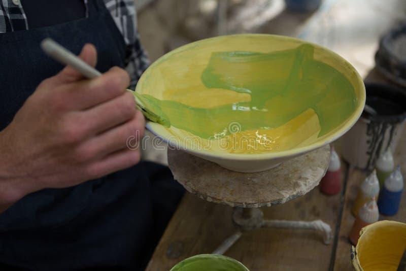 Manliga keramiker räcker att måla en bunke i krukmakeriseminarium royaltyfria bilder