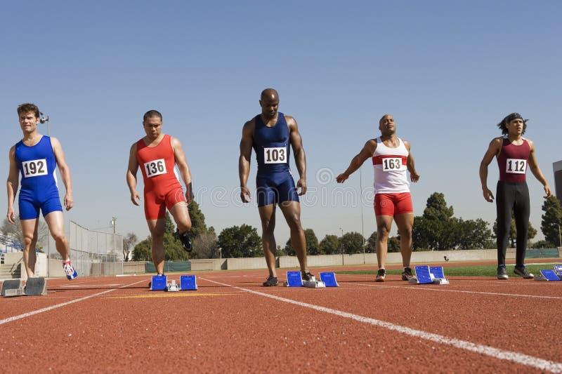 Manliga löpare på den startande linjen royaltyfria bilder