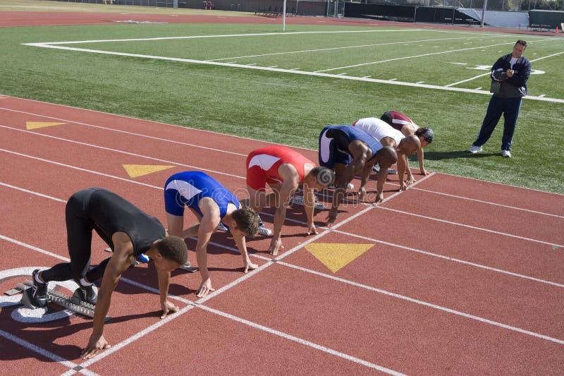 Manliga löpare som förbereder sig för lopp arkivfoton