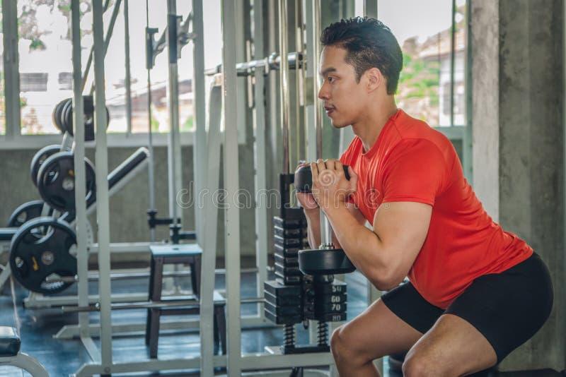 Manliga lyftande dumsbells i idrottshall royaltyfria bilder