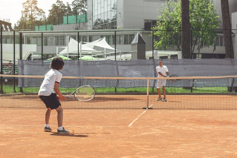 Manliga medlemmar av familjen som spelar tennis royaltyfri bild