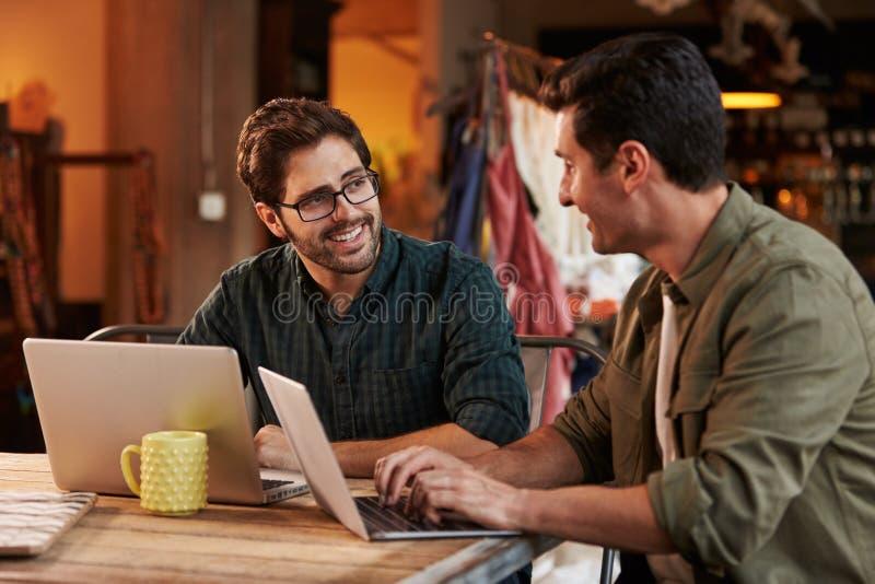 Manliga modeformgivare i möte genom att använda bärbara datorn arkivfoton