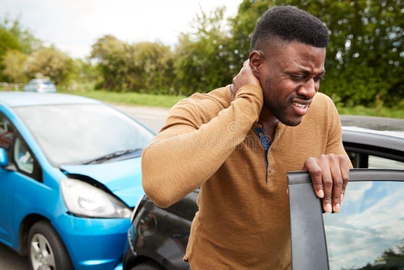 Manliga motorer med whiplash-skada vid bilförkrock som kommer ut ur fordonet royaltyfria foton