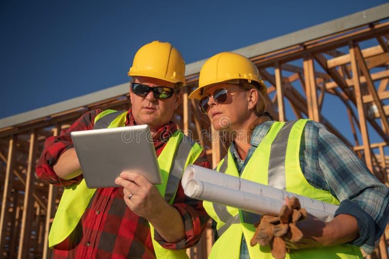 Manliga och kvinnliga byggnadsarbetare som använder datorblocket arkivfoton