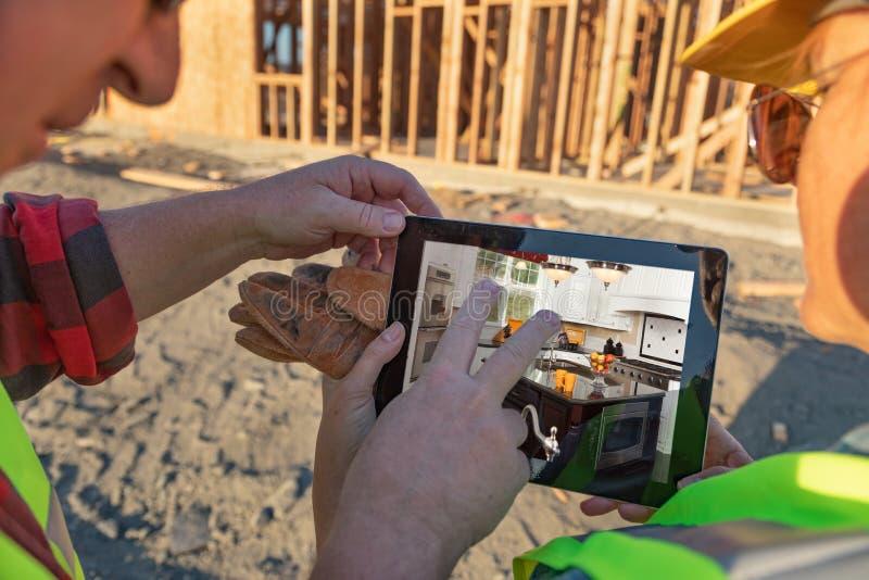 Manliga och kvinnliga byggnadsarbetare som granskar kök på Comput arkivfoto