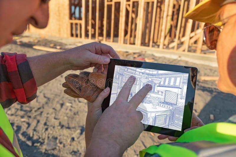 Manliga och kvinnliga byggnadsarbetare som granskar kökteckningen på datorblocket på konstruktionsplatsen royaltyfri foto