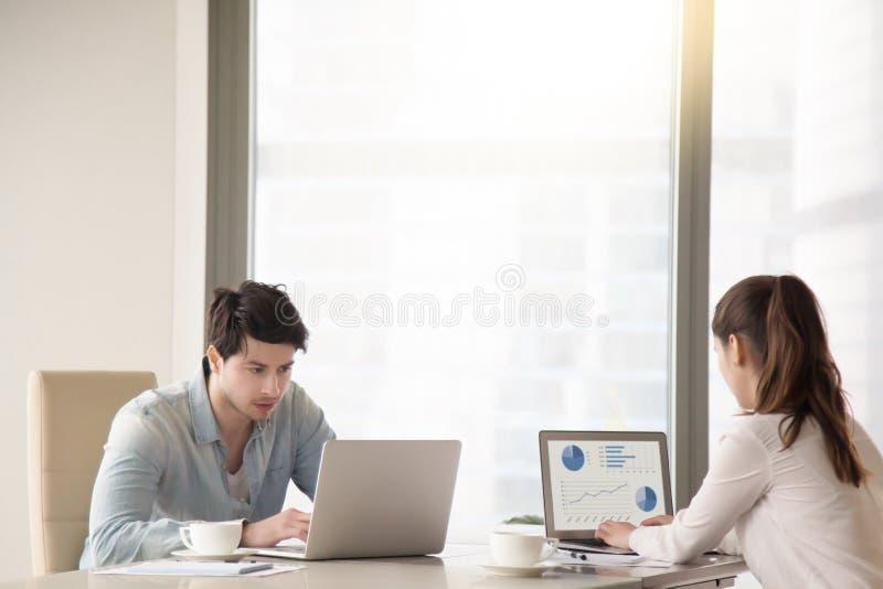Manliga och kvinnliga kollegor som arbetar på kontoret, bordlägger genom att använda bärbara datorer royaltyfria bilder
