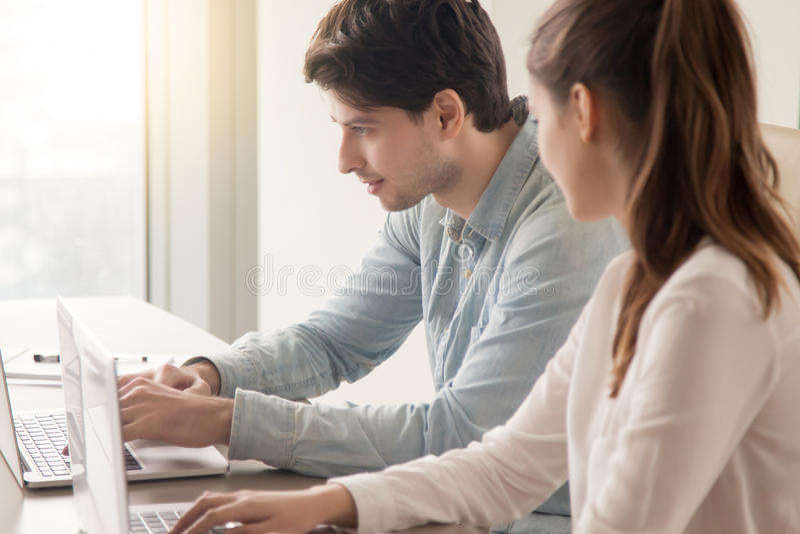 Manliga och kvinnliga kontorsarbetare som använder två bärbara datorer på arbetsplatsen arkivbilder
