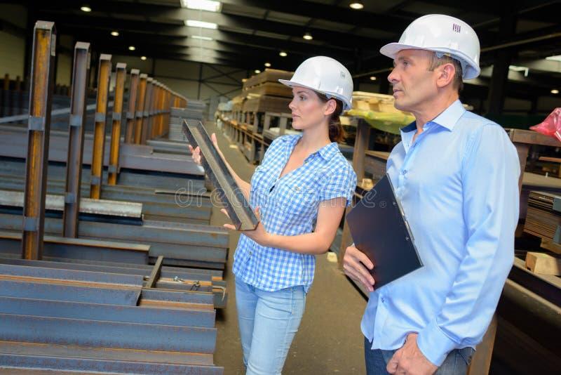 Manliga och kvinnliga ledare i fabrik arkivfoto