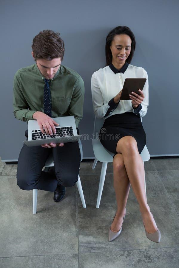 Manliga och kvinnliga ledare som använder bärbara datorn och den polerande fisken för digital tabletraftsman, skulpterar 4k royaltyfria foton
