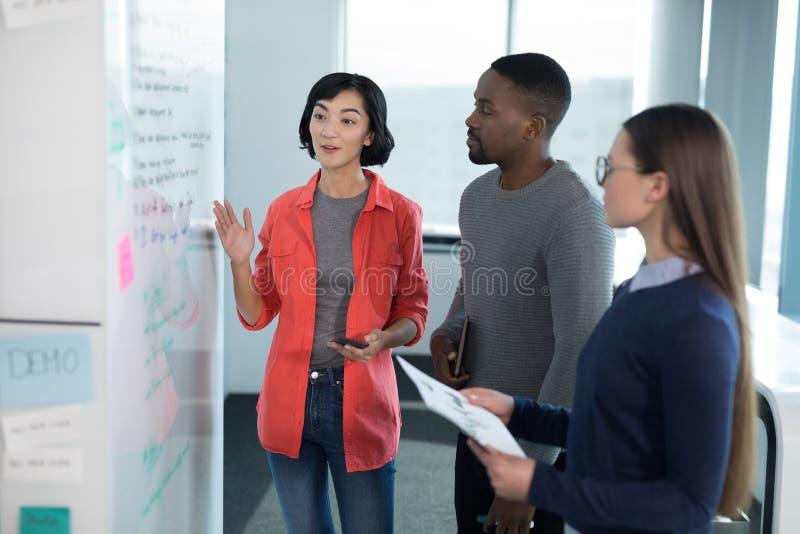 Manliga och kvinnliga ledare som diskuterar på whiteboard royaltyfri fotografi