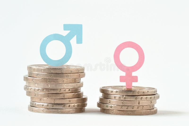 Manliga och kvinnliga symboler på högar av mynt - genuslönjämställdhet royaltyfri fotografi