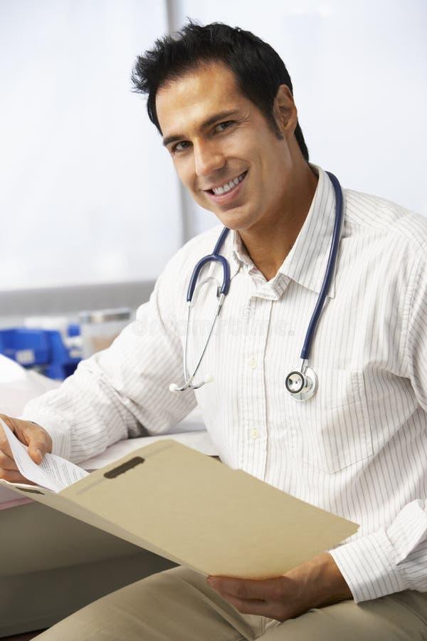 Manliga patientanmärkningar för doktor In Surgery Reading royaltyfria bilder