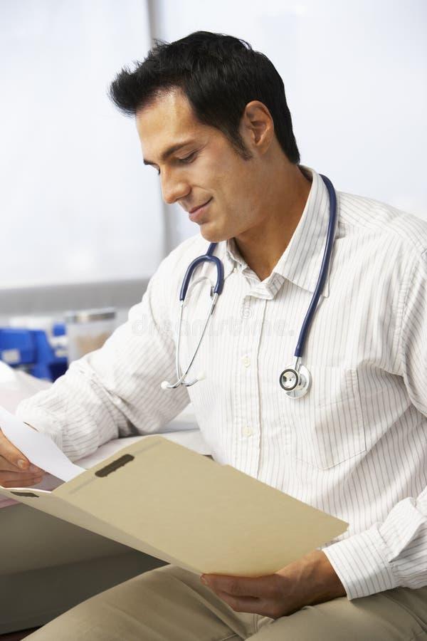 Manliga patientanmärkningar för doktor In Surgery Reading arkivbilder