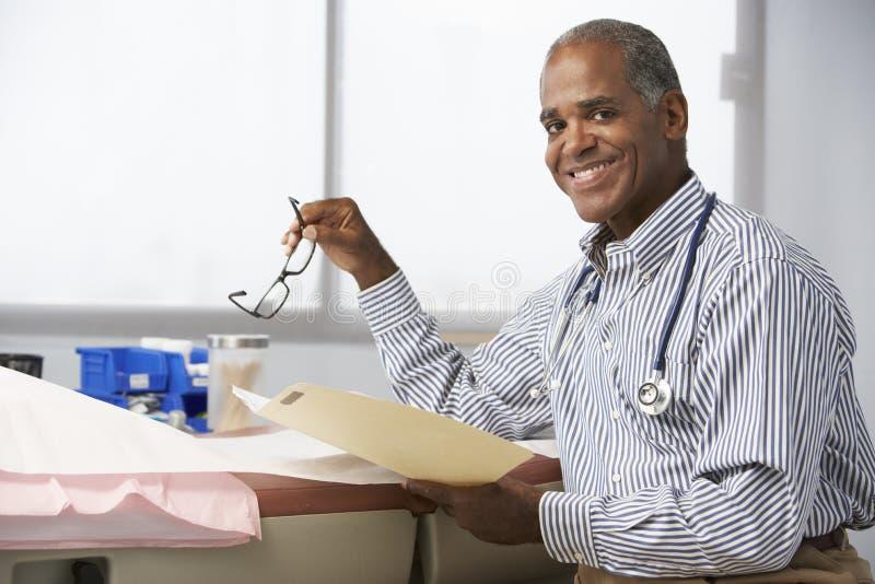 Manliga patientanmärkningar för doktor In Surgery Reading royaltyfri fotografi