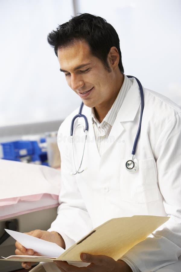 Manliga patientanmärkningar för doktor In Surgery Reading arkivbild