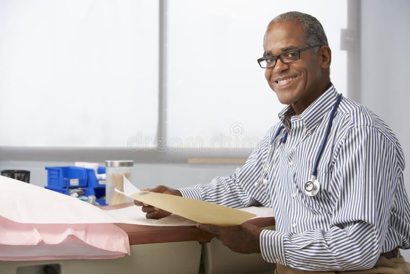 Manliga patientanmärkningar för doktor In Surgery Reading fotografering för bildbyråer