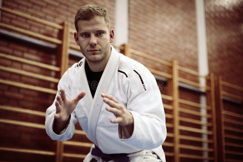 Manliga praktiserande judon i kimono se kameran arkivbild