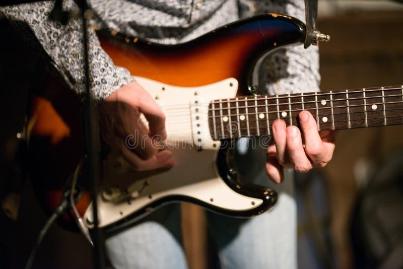 Manliga rader för handinnehavgitarr på etapp arkivfoton