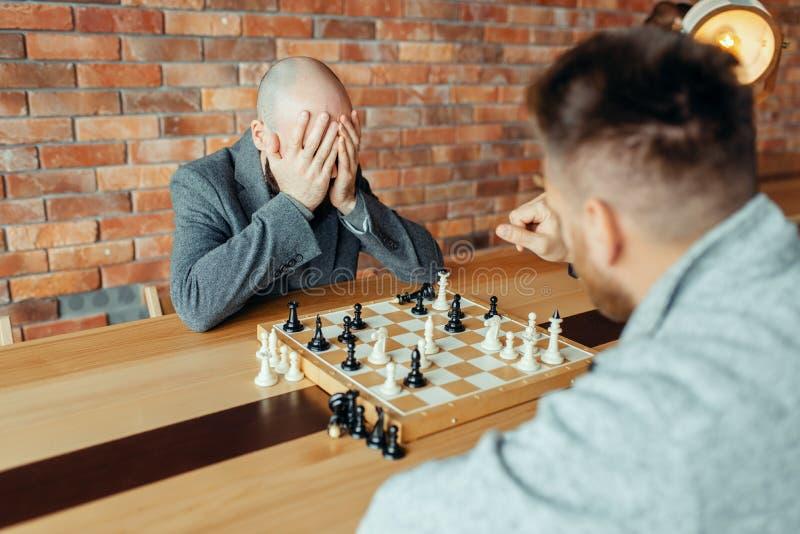 Manliga schackspelare som spelar, vita segrar, kompis royaltyfria bilder