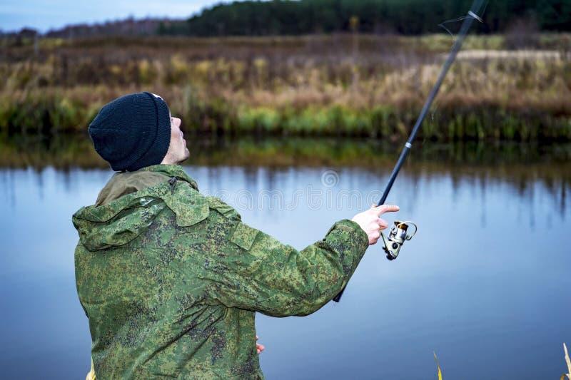 Manliga sportfiskarelås på en snurr fiskar i kallt vatten i offseasonen arkivfoto