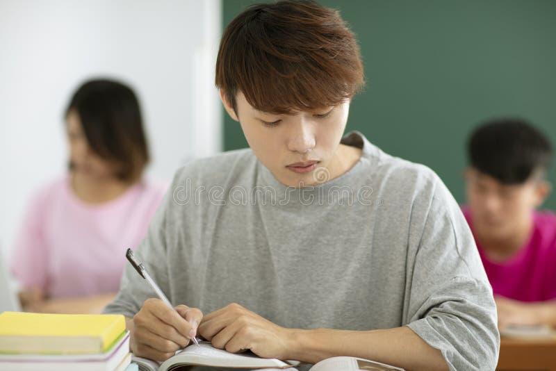 Manliga studenter som studerar i klassrum royaltyfria bilder