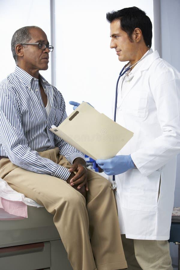 Manliga tålmodiga läsninganmärkningar för doktor In Surgery With arkivfoto