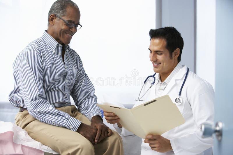 Manliga tålmodiga läsninganmärkningar för doktor In Surgery With fotografering för bildbyråer