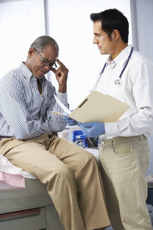 Manliga tålmodiga läsninganmärkningar för doktor In Surgery With royaltyfria bilder