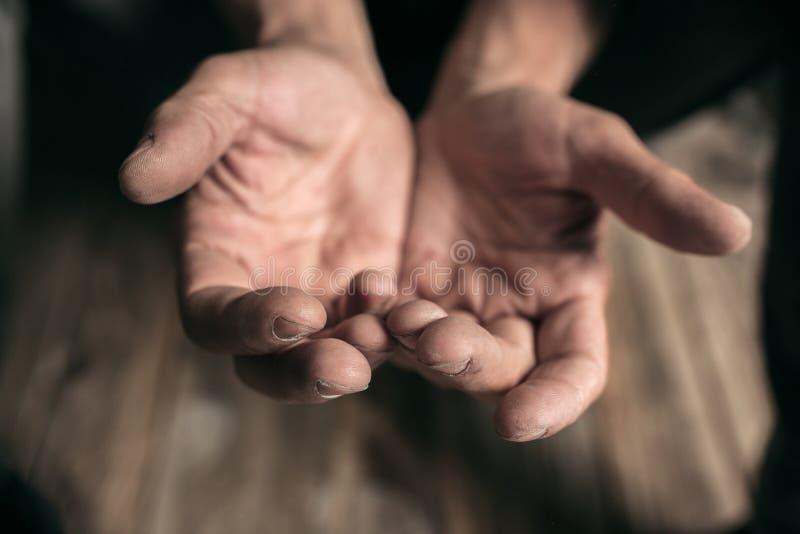 Manliga tiggarehänder som söker pengar på trägolvet på den offentliga banavägen arkivbilder