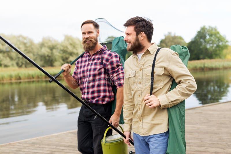 Manliga vänner med förtjänar och metspön på sjön arkivfoton