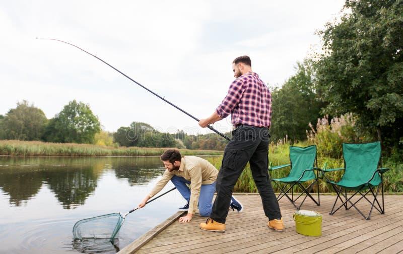 Manliga vänner med förtjänar och metspön på sjön arkivbild