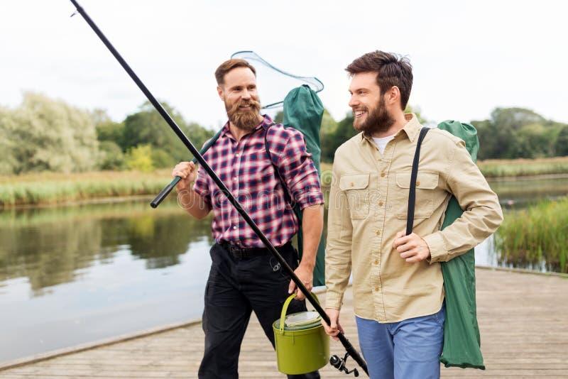 Manliga vänner med förtjänar och metspön på sjön fotografering för bildbyråer