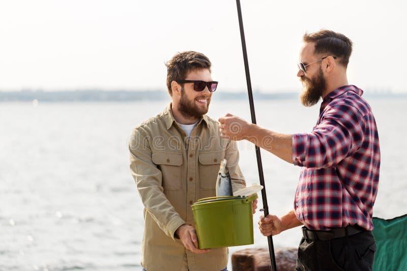 Manliga vänner med fisken och metspön på pir royaltyfri bild