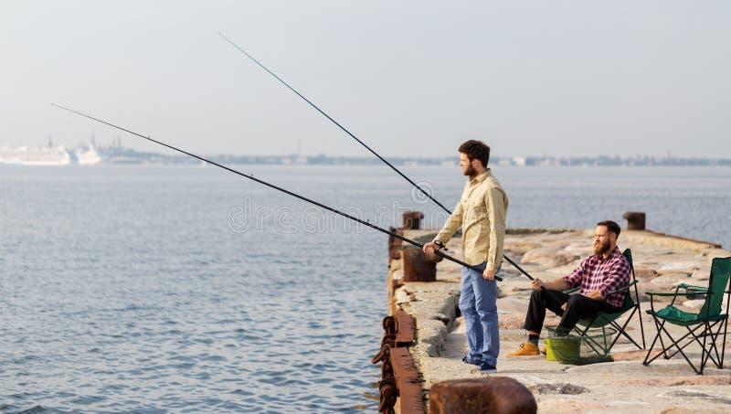 Manliga vänner med metspön på havspir arkivfoton