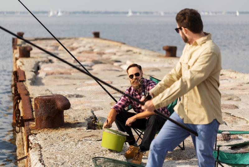 Manliga vänner med metspön på havspir arkivbild